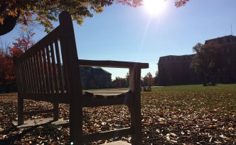 The autumn sun shines on a lonely bench alongside Lafayette's quad. The Farinon Student Center is in the background.
