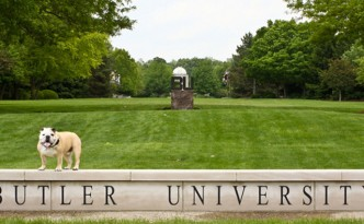 The Butler bulldog stands atop the Butler University sign, with a large grass field in the background.