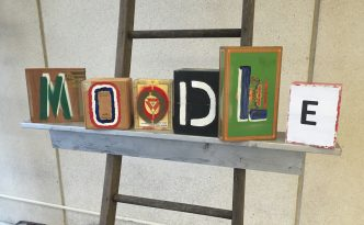 """Stylized art blocks comprise the word """"Moodle"""""""