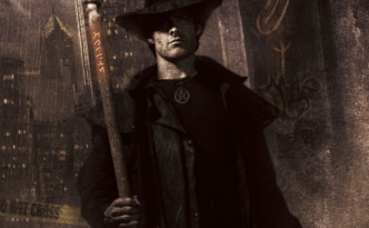 A male human wearing a black overcoat, black hat, and a wizard staff stands in front of a grey/brown urban background.