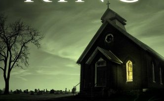 An ominous looking church stands silhouetted against a green/white sky.